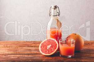 Bottle of grapefruit juice with glass and fruit