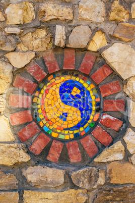 Mosaic symbol of Yin and yang on stone wall.