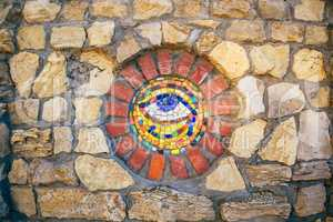 Mosaic Eye of Horus on stone wall.