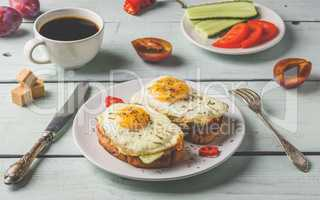 Toasts with vegetables and fried egg and cup of coffee