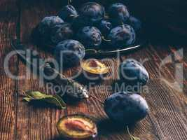 Ripe plums with leaves and knife