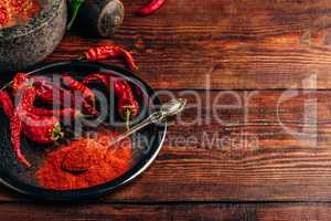 Ground and dried chili peppers on metal plate