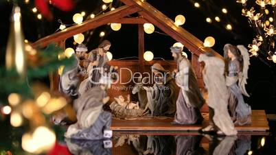 Jesus Christ Nativity scene with atmospheric lights near Christmas tree