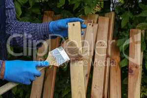 The worker paints wooden slats with protective varnish