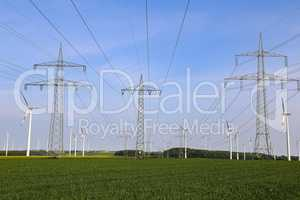 Landscape with high-voltage masts against the blue sky