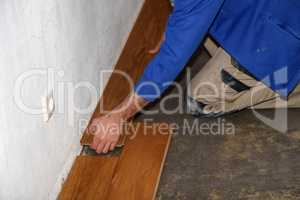Worker laying parquet flooring. Worker installing wooden laminate flooring.
