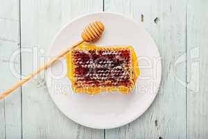 Honeycomb on white plate with honey dipper