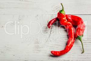 Two chili peppers over wooden background.