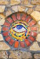 Mosaic Eye of Horus on stone wall.