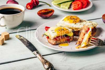 Sandwiches with vegetables and fried egg and cup of coffee