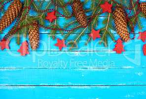 green branches of needles and yellow Christmas garland, red deco