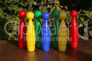 Colorful plastic toy bowling pins on wooden floor