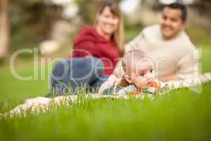 Happy Crawling Baby Boy and Mixed Race Parents Playing in the Pa