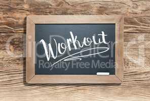 Workout Written on Slate Chalk Board Against Aged Wood Backgroun