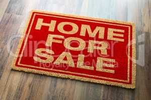 Home For Sale Welcome Mat On A Wood Floor Background