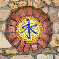 Mosaic religious symbol on wall.