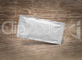 Blank White Condiment Packet Floating on Aged Wood Background