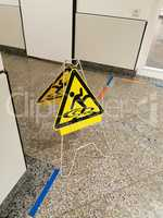 Yellow wet floor warning sign on the floor