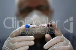 Coronavirus testing - A hand holds a test tube containing a patients sample that has tested positive for coronavirus