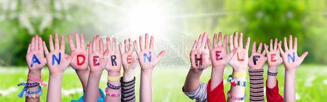 Kids Hands Holding Word Anderen Helfen Means Help Others, Grass Meadow