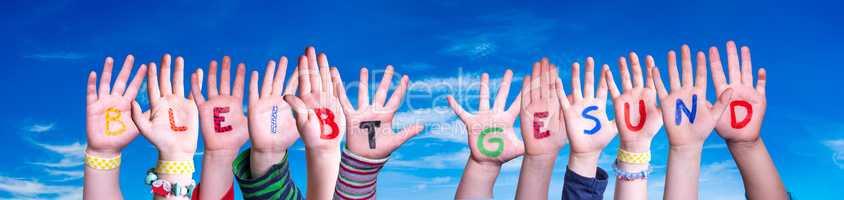 Kids Hands Holding Word Bleibt Gesund Means Stay Healthy, Blue Sky