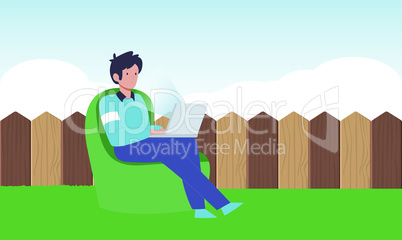 Boy is sitting in a garden and working on laptop