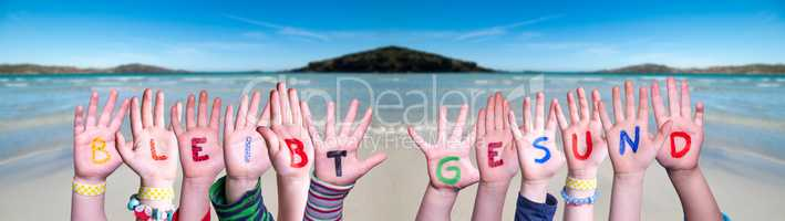 Kids Hands Holding Word Bleibt Gesund Means Stay Healthy, Ocean Background