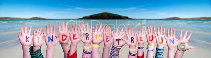 Kids Hands Holding Word Kinderbetreuung Means Child Day Care, Ocean Background