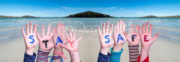 Kids Hands Holding Word Stay Safe, Ocean Background