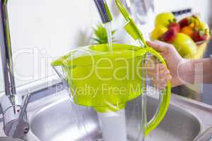 Woman filling water filter jug in the kitchen
