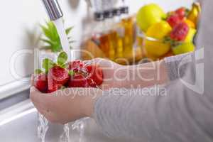 Woman washing strawberries in the kitchen