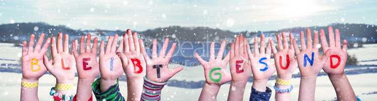 Kids Hands Holding Word Bleibt Gesund Means Stay Healthy, Snowy Winter Background