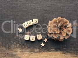 Pine cone and wooden dices with the words God Jul, Scandinavian